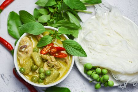 Thai food green curry chicken on soup bowl and thai rice noodles vermicelli with ingredient herb vegetable / asian food on the table