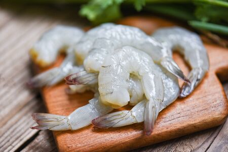 raw shrimp on wooden cutting board background for cooking / close up fresh shrimps or prawns , Seafood shelfish