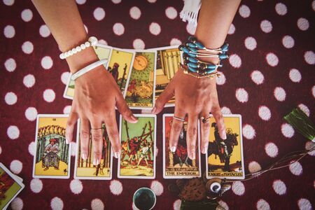 Tarot cards reading divination Psychic readings and clairvoyance concept / fortune teller hands , and Horoscopes