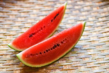 watermelon slice on wood background / close up fresh watermelon pieces tropical summer fruit