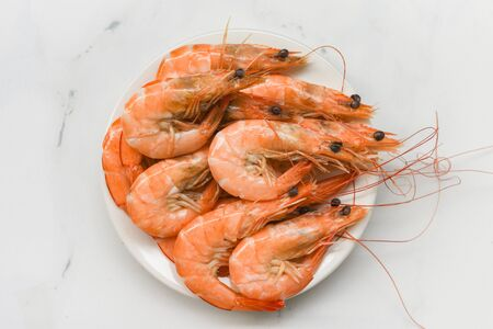 Shrimp on white plate / cooking seafood shrimps prawns served on a food table background