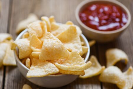 prawn crackers chips on white bowl and wooden table background / homemade crunchy prawn crackers or shrimp crisp rice and ketchup for traditional snack