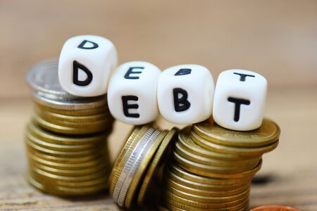 Debt concept with block debt and stacked coins on wooden table background