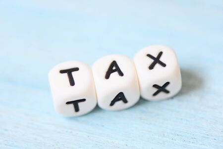 Taxes concept with block tax on wooden table background