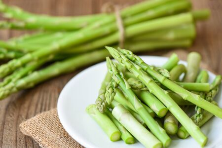 Asparagus on white plate and wooden background / Fresh green asparagus sliced for cooking food
