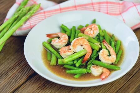 Asparagus Shrimp Seafood Cooked Health Food / Stir fried shrimps with asparagus green on white plate and wooden table background