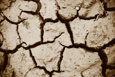 Cracks of the dried soil in arid season / Arid soil , Cracked earth texture of ground broken and rough surface mud clay top view  Фото со стока