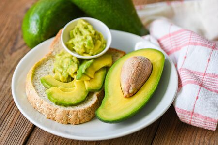 Avocado sliced half and avocado dip mashed on white plate background fruits healthy food concept / avocado toast