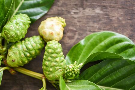 noni fruit on wooden background / fresh ripe and raw noni leaf , Great morinda (Noni) or Morinda citrifolia