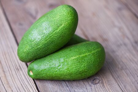 Fresh green avocado on the wooden table / Fruits healthy food concept