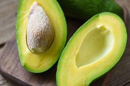 Avocado sliced half on wooden cutting board for avocado salad / Fruits healthy food concept