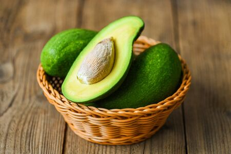 Avocado sliced half in basket on the wooden table / Fruits healthy food concept