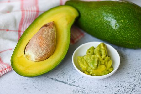 Avocado sliced half and avocado dip mashed on table background / Fruits healthy food concept