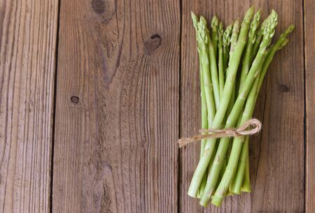 Asparagus on wooden background / Fresh green asparagus Фото со стока