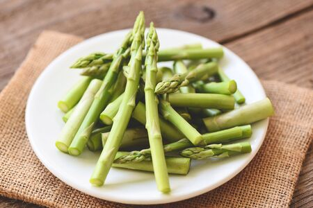 Asparagus on white plate and wooden background / Fresh green asparagus sliced for cooking food Фото со стока