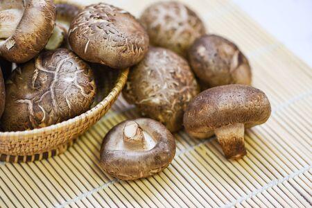 Fresh mushrooms on basket and wooden table background / Shiitake mushrooms Фото со стока
