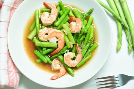 Asparagus Shrimp Seafood Cooked Health Food / Stir fried shrimps with asparagus green on white plate  Фото со стока
