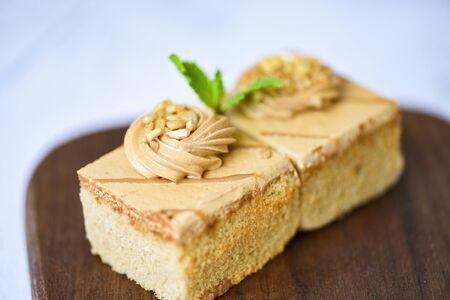 coffee cake delicious dessert with mint leaf and nuts topping on wooden