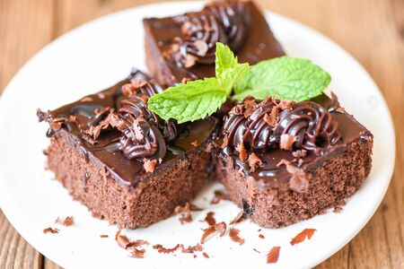 Cake chocolate delicious dessert served on the table / cake slice on white plate with topping chocolate and mint leaf