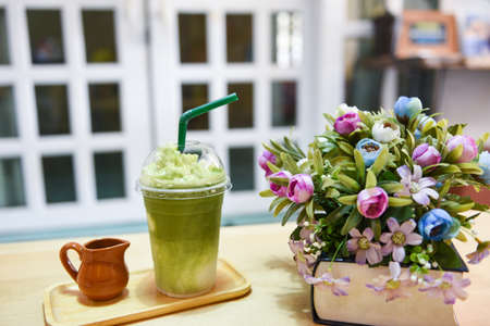 Green tea smoothie / Matcha green tea with milk on plastic glass on the table in a cafe Standard-Bild