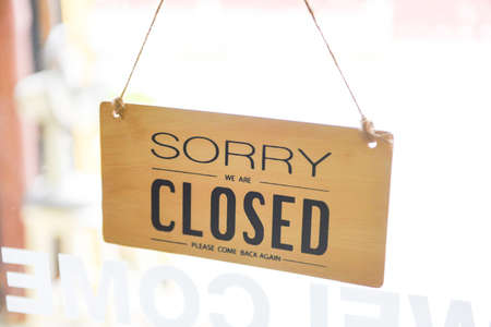 Closed shop sign / Sorry we're closed sign hanging on cafe glass door