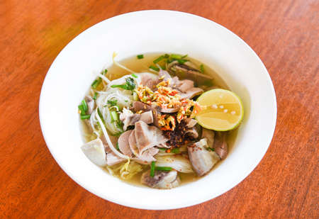 delicious noodles bowl / close up of vermicelli noodles soup spicy with pork stew vegetable and lemon in bowl traditional thai and chinese style food of asia , Pork offal , Liver pork intestines Standard-Bild