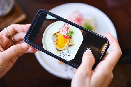 Food photography woman hands make photo cake with smartphone / taking photo food for post and share on social networks with camera smart phone in restaurant Standard-Bild