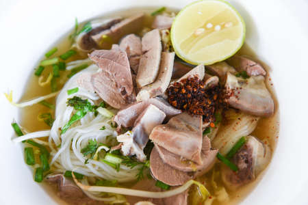 vermicelli noodles soup spicy with pork stew vegetable and lemon in bowl traditional thai and chinese style food of asia , Pork offal , Liver pork intestines / delicious noodles bowl Standard-Bild