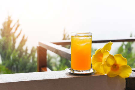 orange juice glass with yellow flower on balcony with rain drops in the morning