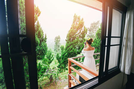woman on the balcony and taking photo sunrise on nature green view from window / Morning terrace and girl with sunlight