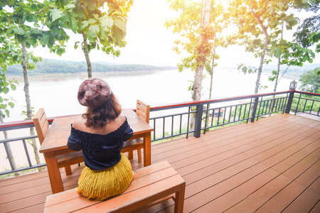 Woman sitting on a chair on the balcony with nature view tree forests and rivers / Morning terrace wooden and girl