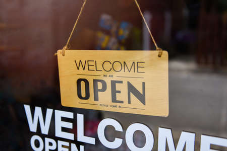 Open shop sign / Welcome open sign hanging on cafe glass door