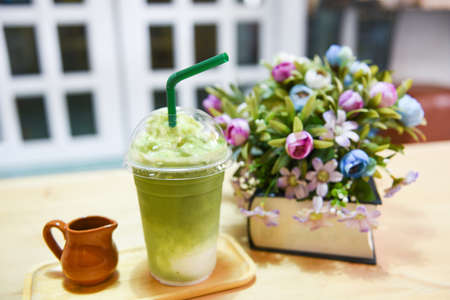 Matcha green tea with milk on plastic glass on the table in a cafe / Green tea smoothie Standard-Bild