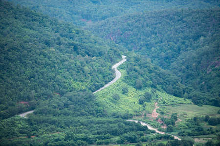 Road to mountain / A long straight road leading towards a nature green tree on the mountains , Asphalt road in Thailand , top view Standard-Bild