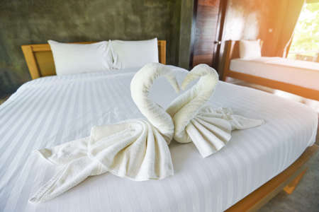 White clean bath towel on bed decoration interior of bedroom / White towel on bed in guest room for hotel customer
