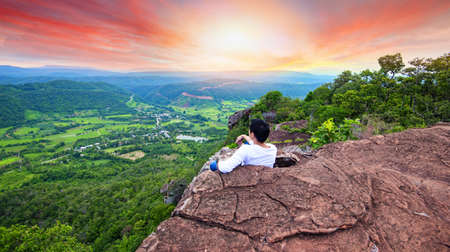 Man on mountain / Hiker sitting on the rock valley cliff , Man watch over sunset valley to bright sun on village in countryside Asia Tourist looking to misty valley below landscape beautiful mountain Standard-Bild