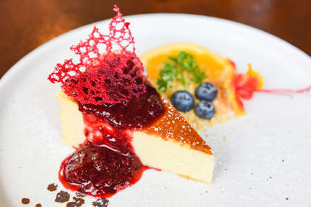 Cheese cake slice with raspberry sauce on withe plate / cheesecake fruit delicious dessert