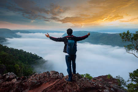 Backpacking man on mountain / Hiker on rock above valley , Man watch over misty morning valley to bright morning Sun Tourist looking to misty valley bellow cold landscape weather Beautiful mountain