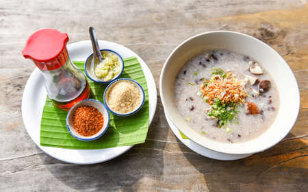 Mush or rice porridge / Boiled rice with pork shiitake mushrooms and vegetables with seasoning food sauce on wooden table