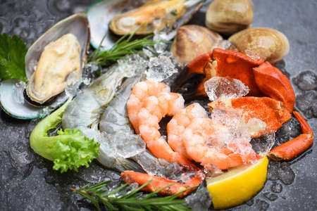 Fresh raw seafood buffet with lemon rosemary ingredients herb and spices / Seafood shellfish on ice frozen with shrimps prawns crab claws shell clam squids octopus and mussels at the restaurant