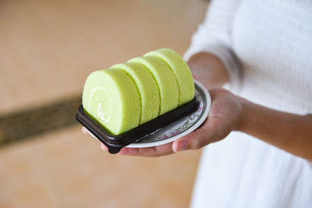 cake roll on plate / woman served green cake roll pandan with cream