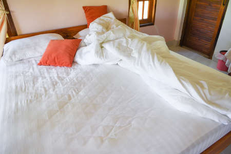 Unmade bed sheet of the crease and pillow white blanket in the bedroom after sleep on top view / Wrinkled fabric sunlight in the morning bed Stock fotó