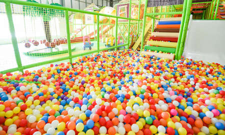 Children playground indoor at amusement park with colorful balls for playing / Inside the beautiful kids playground ball colored plastic of game room