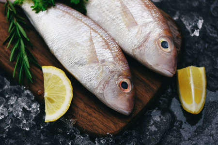 Fresh raw fish with ingredients lemon rosemary and lettuce for making cooked food on ice at market sea bream seafood fish frozen