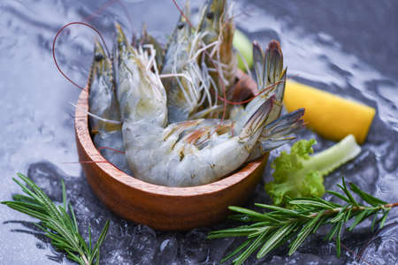 Fresh shrimp on bowl with rosemary ingredients herb and spices for cooking seafood / Raw shrimps prawns on ice frozen at the seafood restaurant Zdjęcie Seryjne