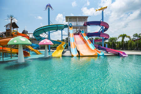 water park slide with swimming pool at amusement park / colored plastic water slides with pool in outdoor aqua park Zdjęcie Seryjne