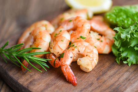 Salad shrimp grilled delicious seasoning spices on wooden cutting board background appetizing cooked shrimps baked prawns , Seafood shelfish with rosemary lemon and lettuce