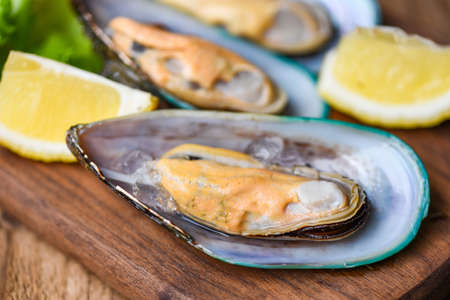 Fresh mussels on wooden and lemon shellfish steamed mussels