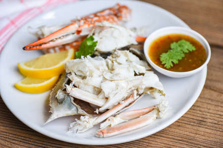 Crab meat / Cooked crab claws and legs on white plate and seafood sauce on the table , blue swimming crab