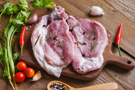 fresh pork / raw pork meat rosemary on white plate with herbs and spices tomato vegetables